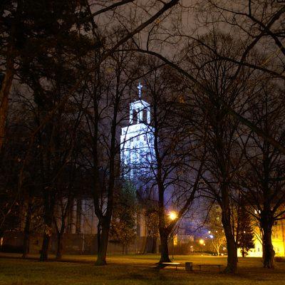 Noční pohled na věž kostela sv. Hedviky zářící modře